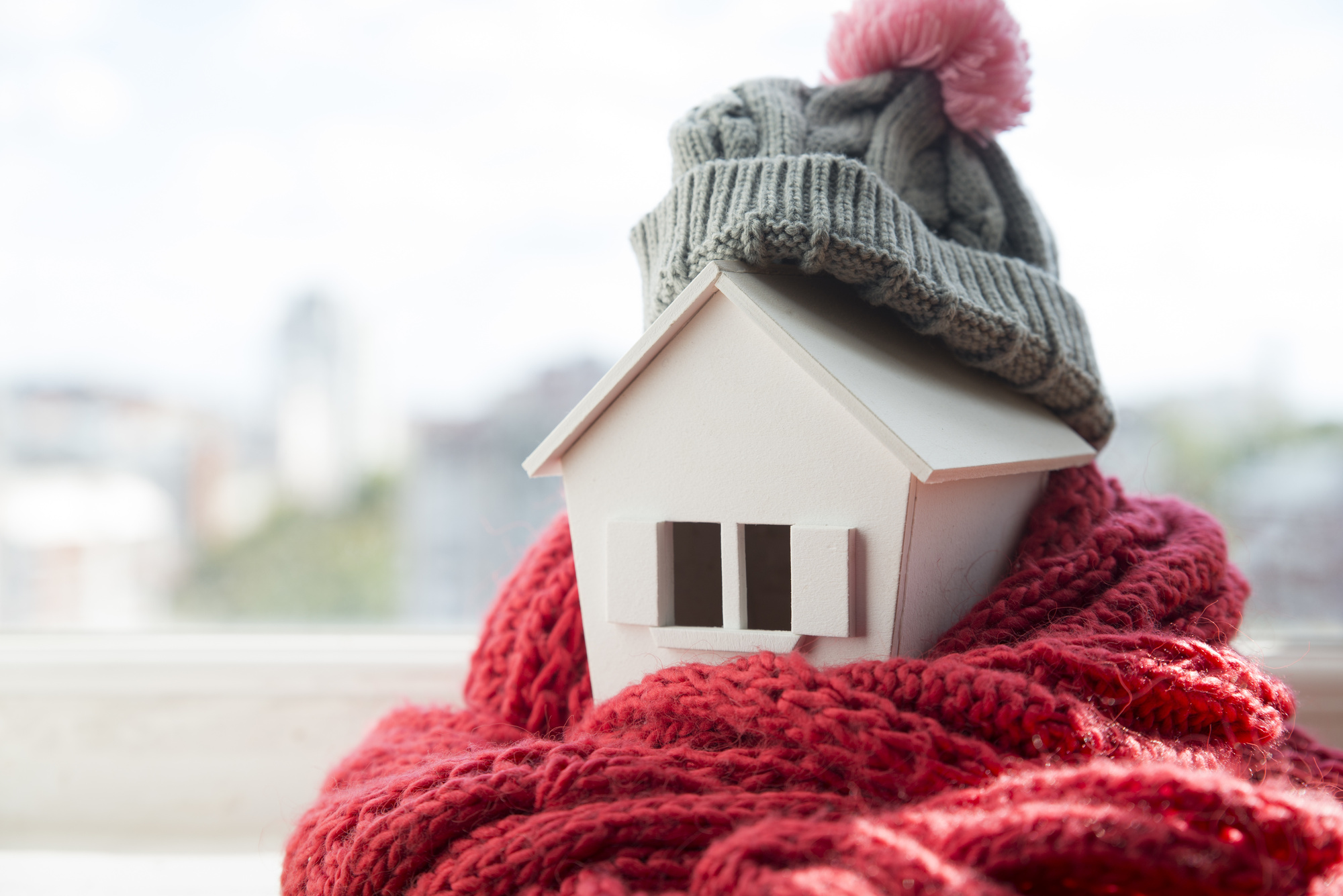 house in winter – heating system concept and cold snowy weather with model of a house wearing a knitted cap